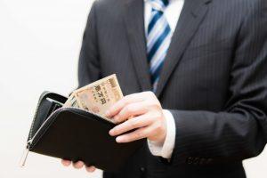 財布からお金をとりだす男性