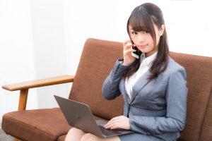 パソコンを持ちながら電話する女性