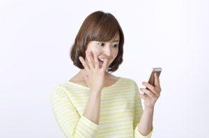携帯をみて驚く女性